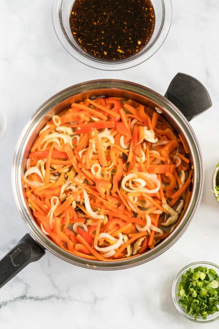 Carrots and onions cooking in a large frying pan.