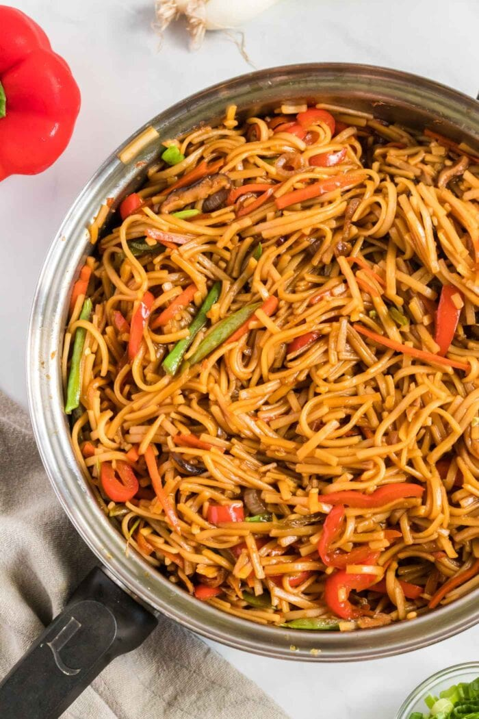 Rice noodles cooked in sauce with veggies in a large frying pan.
