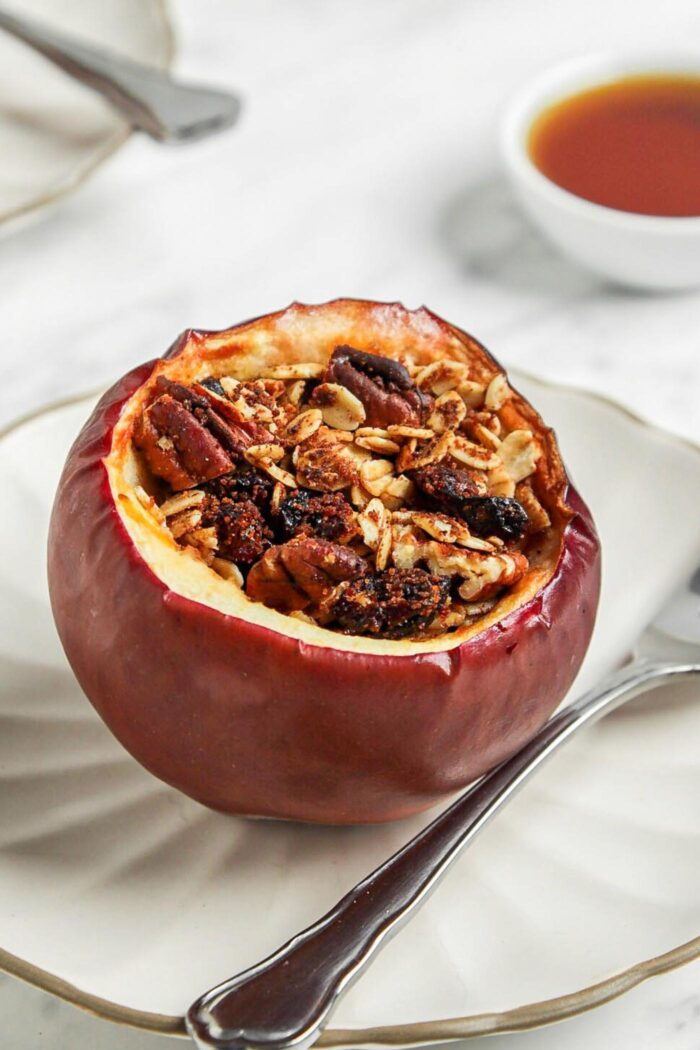 Baked stuffed apple on a small plate with a spoon.