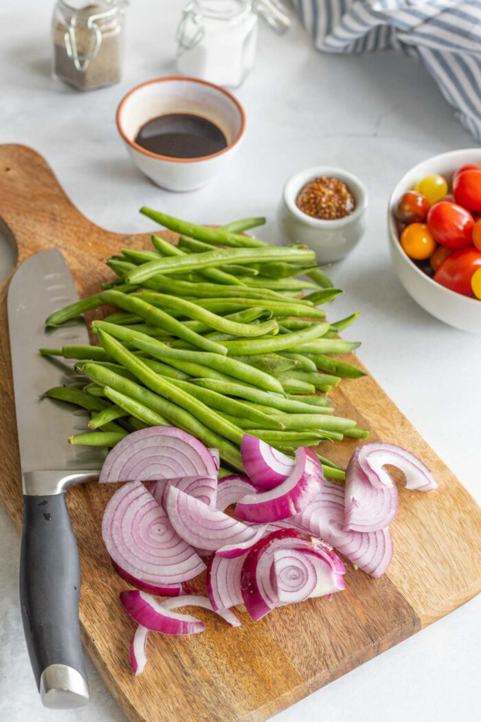 Chopped onions and green beans on a cutting board.