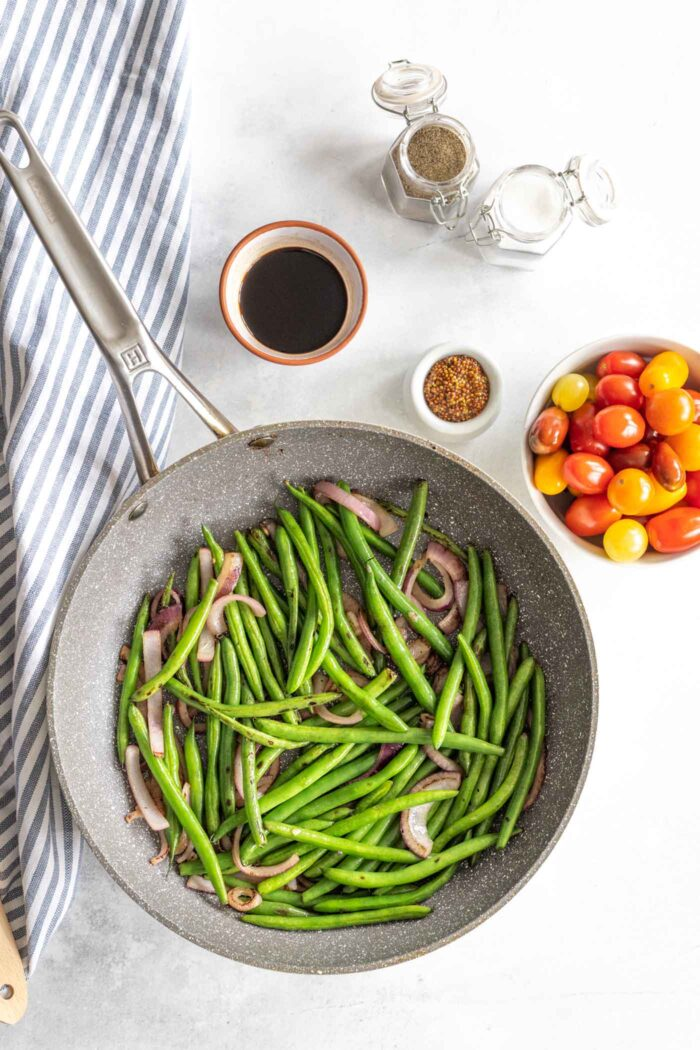 Green beans and onions cooking in skillet.