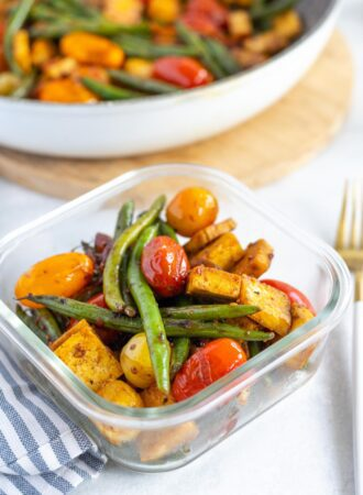 Tofu, tomatoes, green beans and tomatoes in a glass storage container.