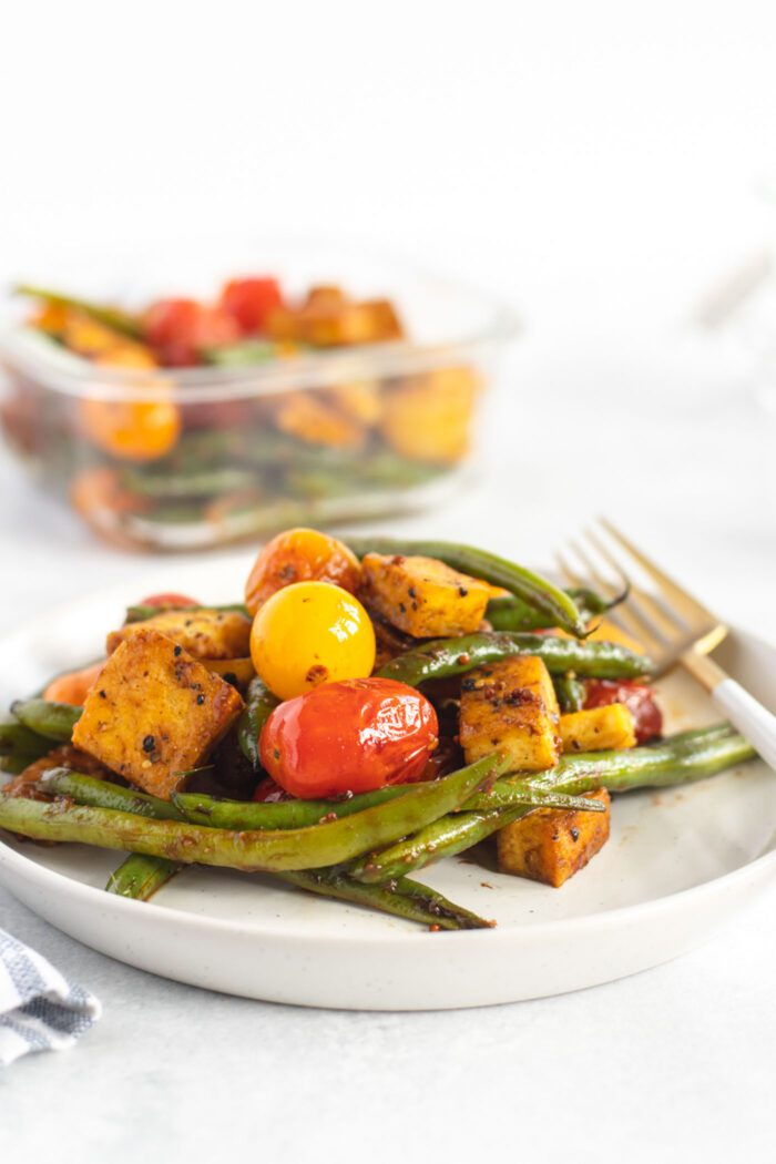 Tofu, green beans and tomatoes on a small plate with a fork.