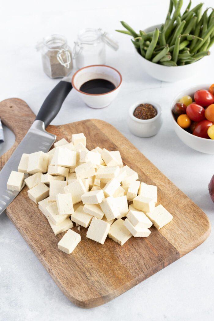 Chopped tofu on a cutting board.