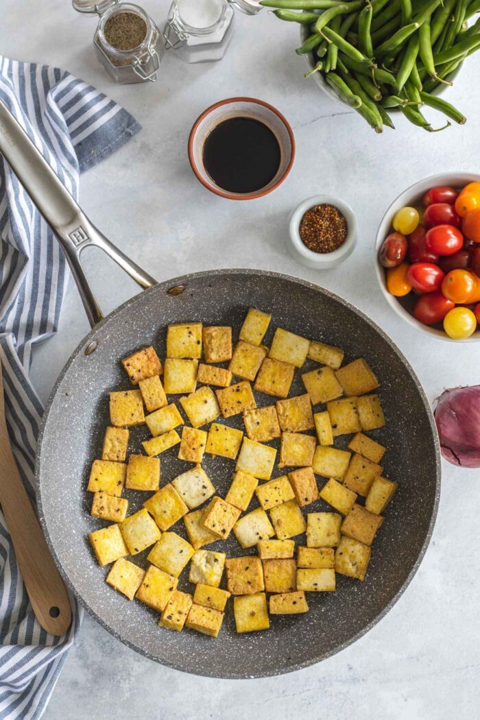 Tofu cooking in a skillet.