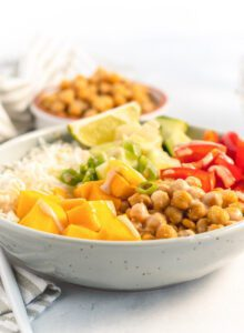 Bowl of rice, mango and fresh vegetables topped with sauce.