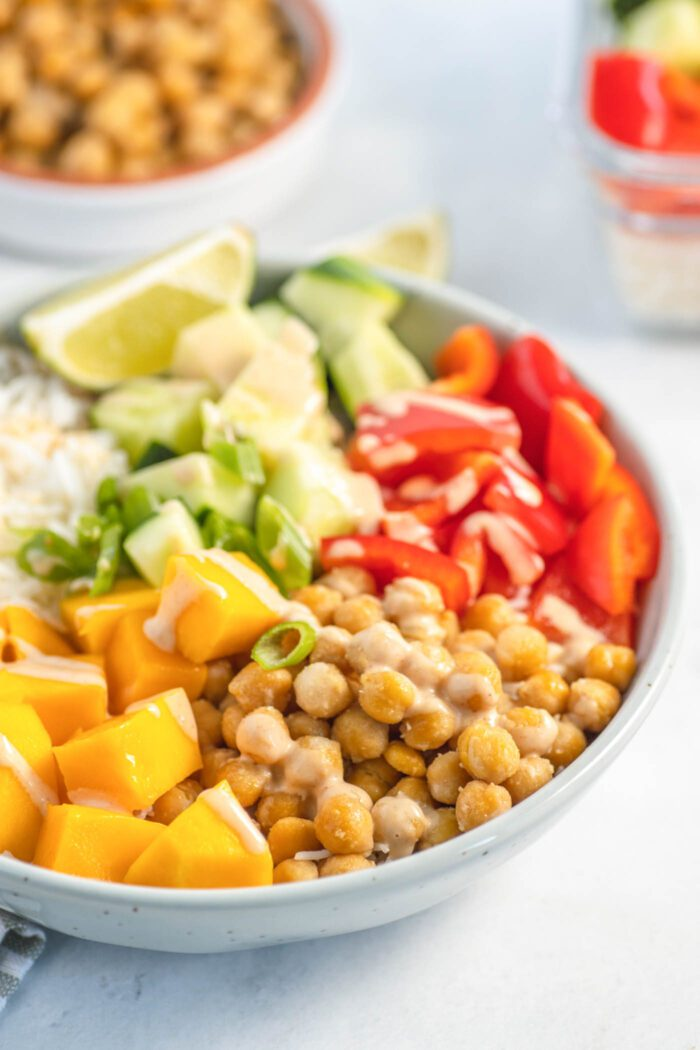 Bowl of chickpeas, mango, rice, bell pepper, cucumber and sauce.