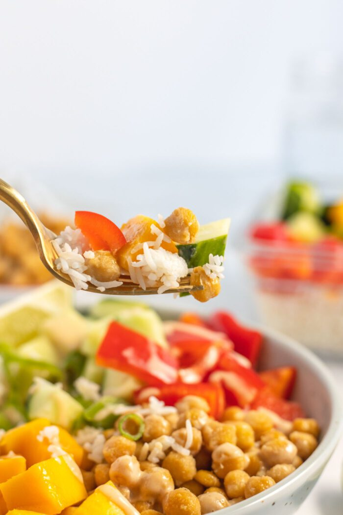 Forkful of rice, cucumber, chickpeas and bell pepper.