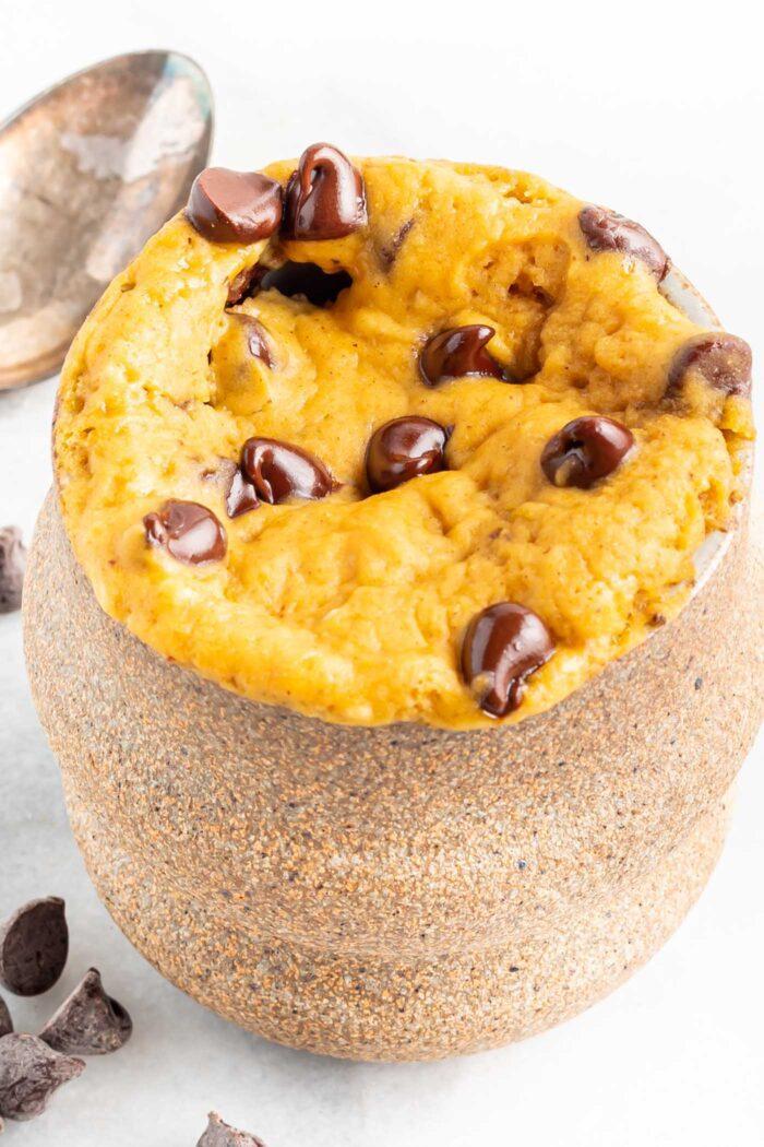 Close up of a chocolate chip pumpkin cake in a mug.