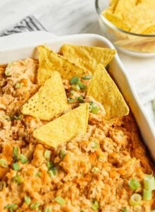 Overhead view of a dish of baked buffalo dip topped with scallions with some tortilla chips in the dip.