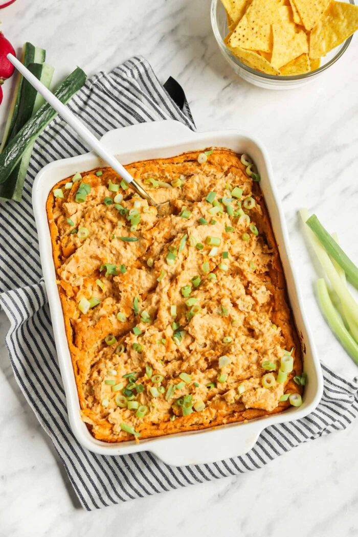 Baked buffalo chicken dip topped with green onions in a baking dish.