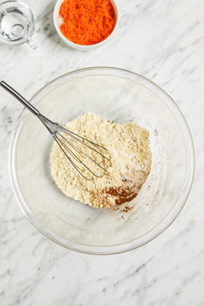 Dry pancake batter ingredients mixed in a mixing bowl with a whisk.