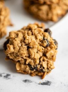Close up of an oatmeal cookie with cranberries and walnuts in it.
