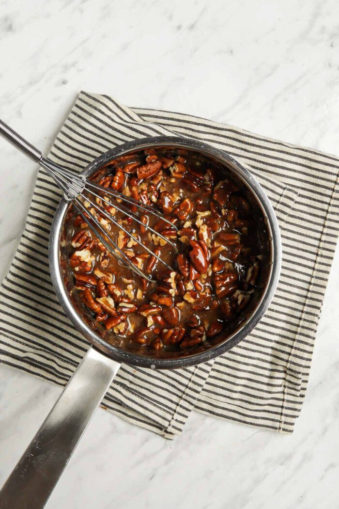 Caramel with chopped pecans in a small saucepan with a whisk.