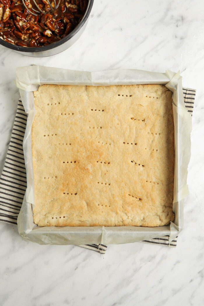 Shortbread dough with small holes from a fork poked in it pressed into a baking pan.