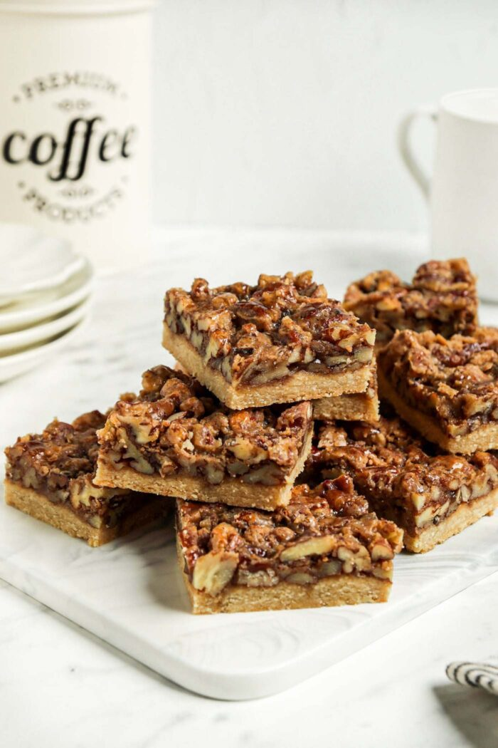 Stack of pecan squares on a small cutting board. Jar of coffee and stack of plates are in the background.