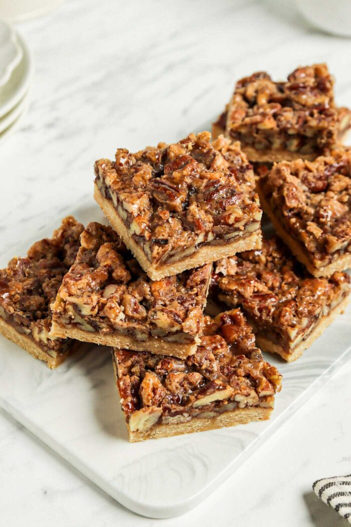 Stack of pecan pie squares on a cutting board.