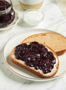 Piece of toast topped with blueberry chia jam. Jar of blueberry jam and a mug of coffee in the background.