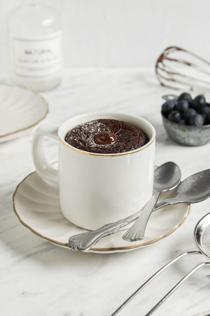 Chocolate mug cake on a small plate with 2 spoons resting on plate.