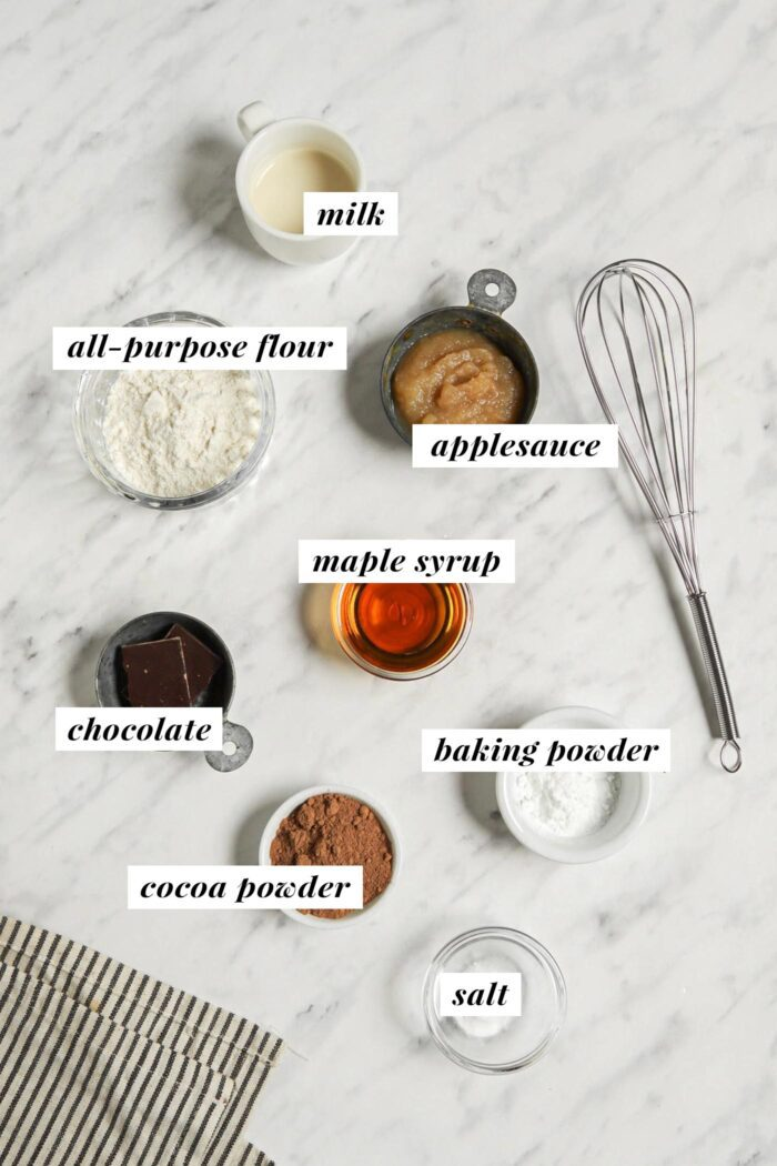Visual list of ingredients for making a chocolate mug cake recipe. Each ingredient is labelled with text.