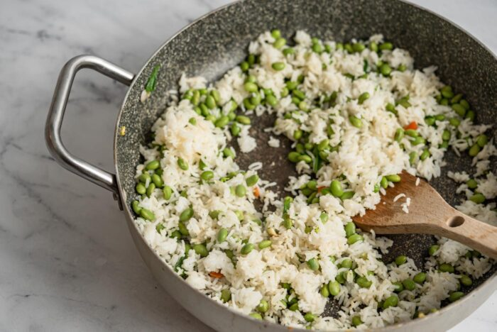 Rice and edamame cooking in a skillet.