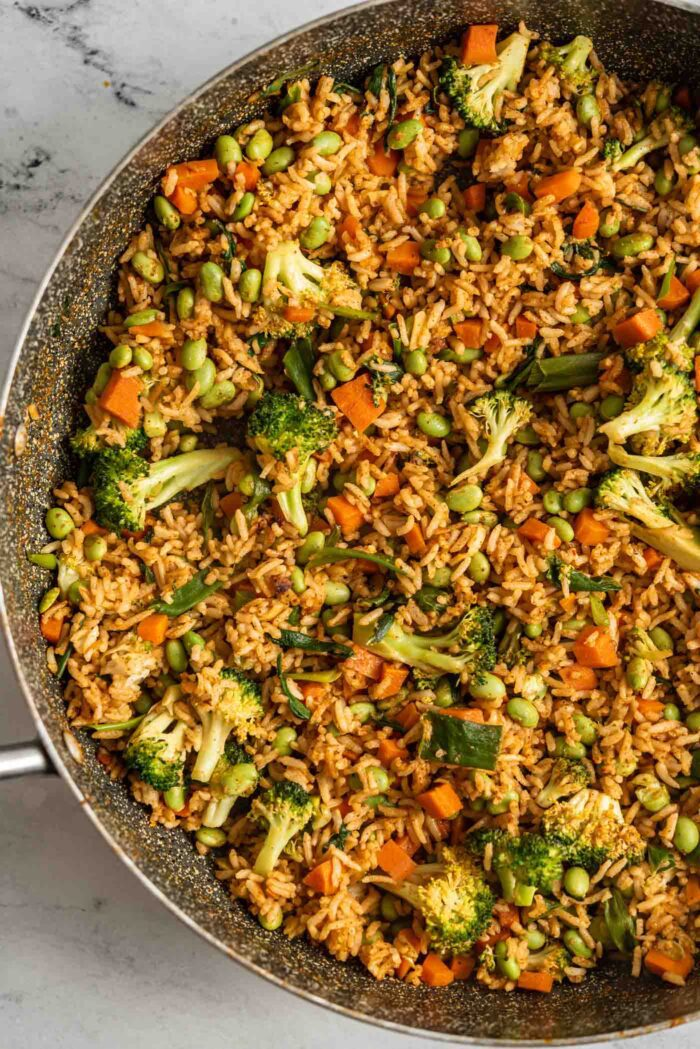 Curry fried rice with vegetables and edamame cooking in a large skillet with a wooden spoon.