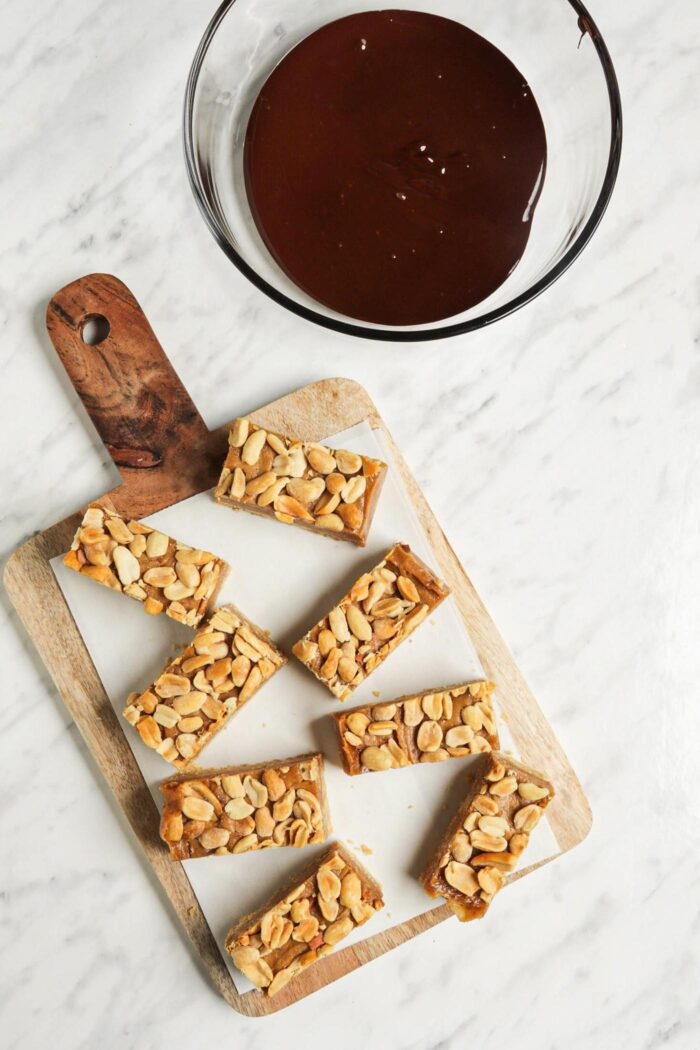 Sliced peanut candy bars on a cutting board beside a bowl of melted chocolate.