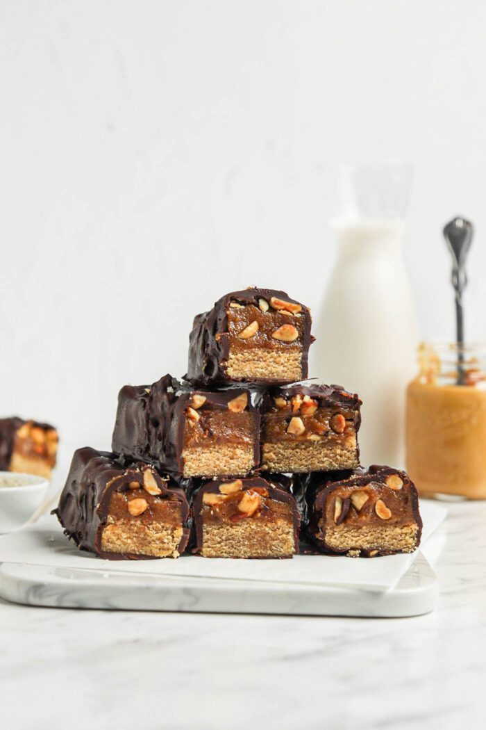 Stack of homemade Snickers bars with a cookie base, caramel layer and chocolate coating.