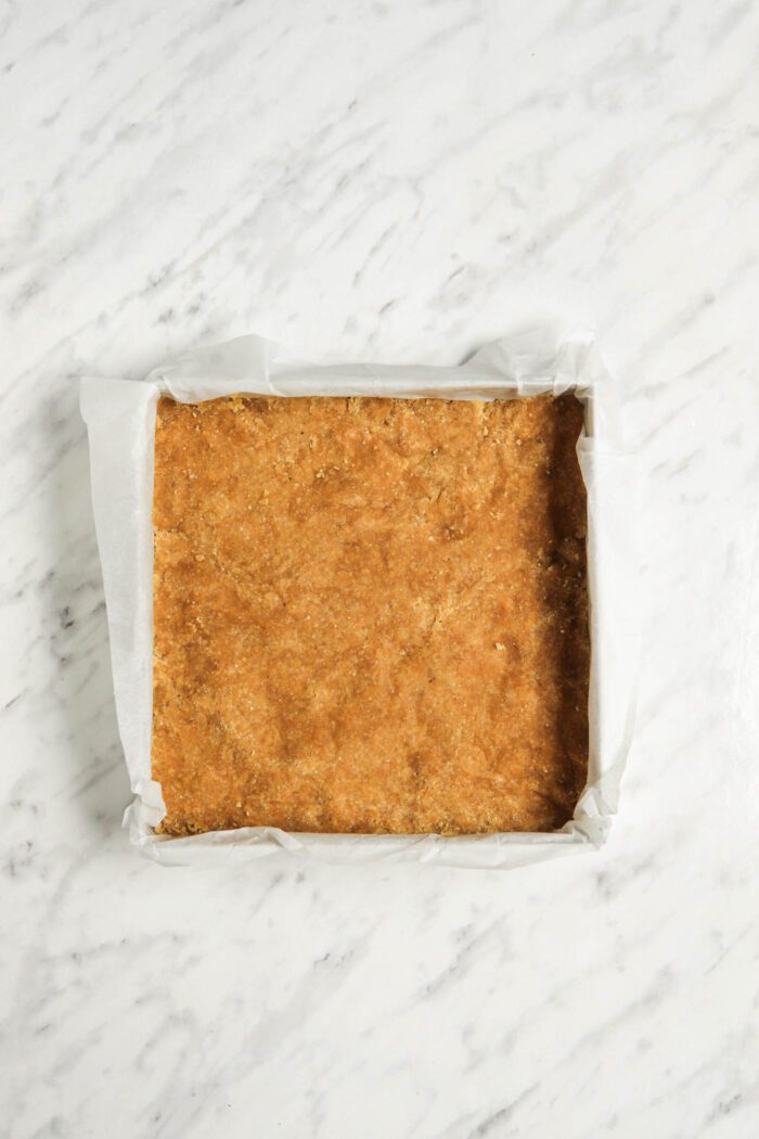 Dough pressed firmly into a square baking pan.