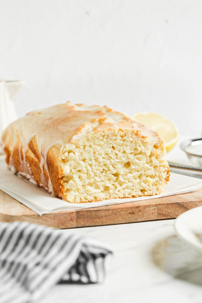 Sliced lemon pound cake topped with glaze on a cutting board lined with parchment paper.