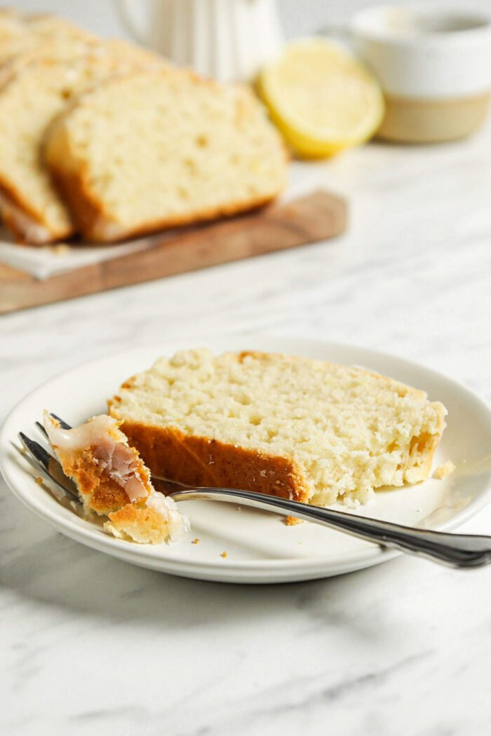 Slice of lemon drizzle cake with icing on a small plate with a fork.