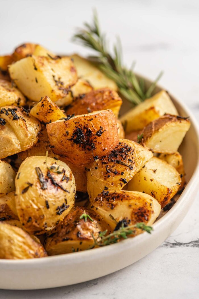 Close up of a bowl of rosemary lemon roasted potatoes with a sprig of rosemary in the bow.