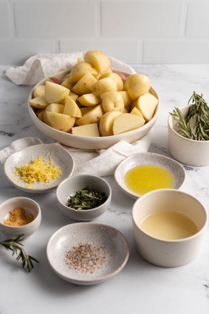 Various bowls containing chopped potatoes, lemon zest, salt, pepper, rosemary, oil and lemon juice.