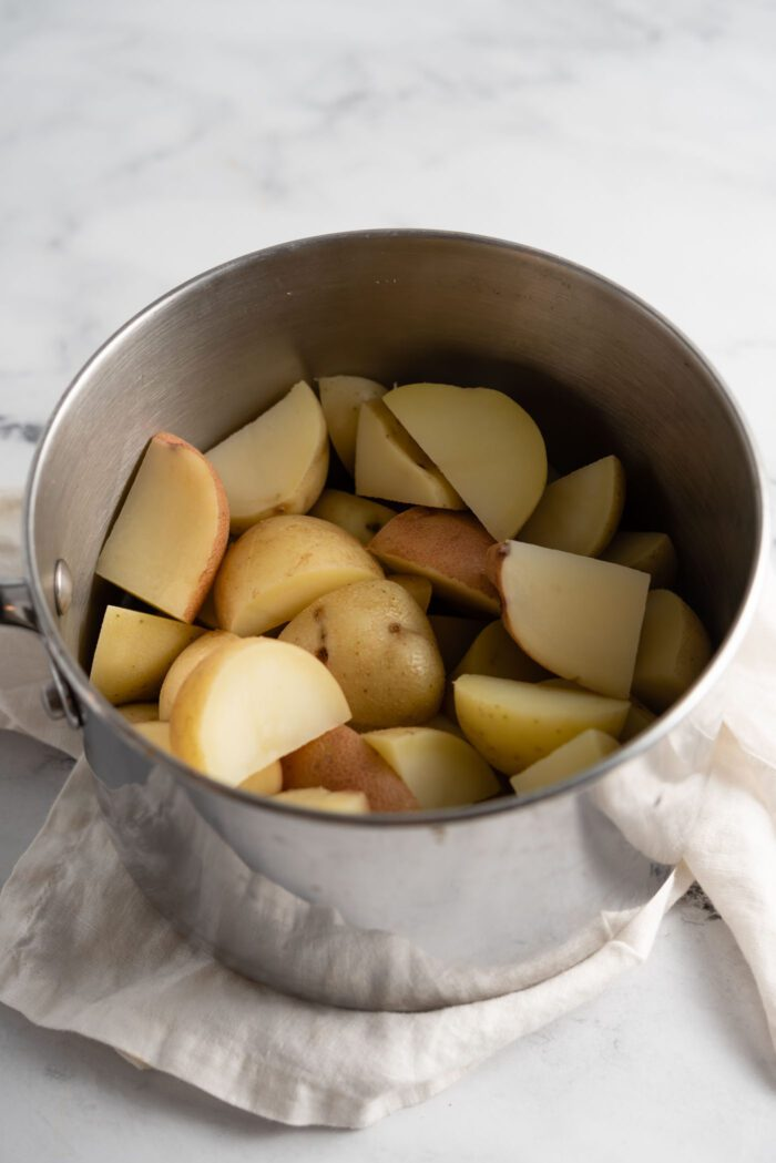Boiled chunks of potato in a small pot.