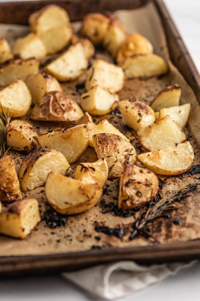 Crispy rosemary roasted potatoes on a baking tray.