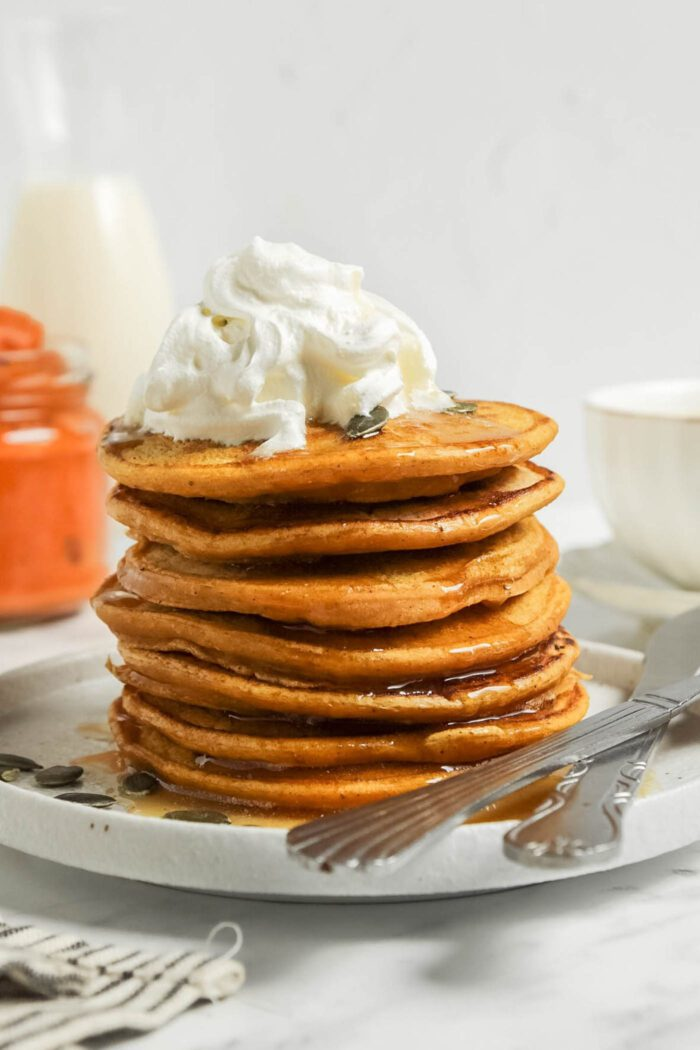 Stack pumpkin pancakes topped with whipped cream and maple syrup.