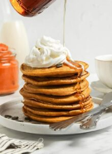 Hand pouring maple syrup from a jar over a stack of pumpkin pancakes topped with whipped cream.