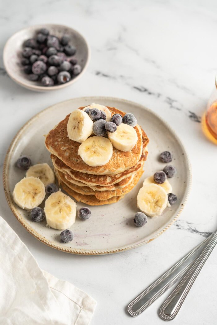 Stack of quinoa flour pancakes topped with blueberries and banana on a small plate. Small dish of blueberries in the background.