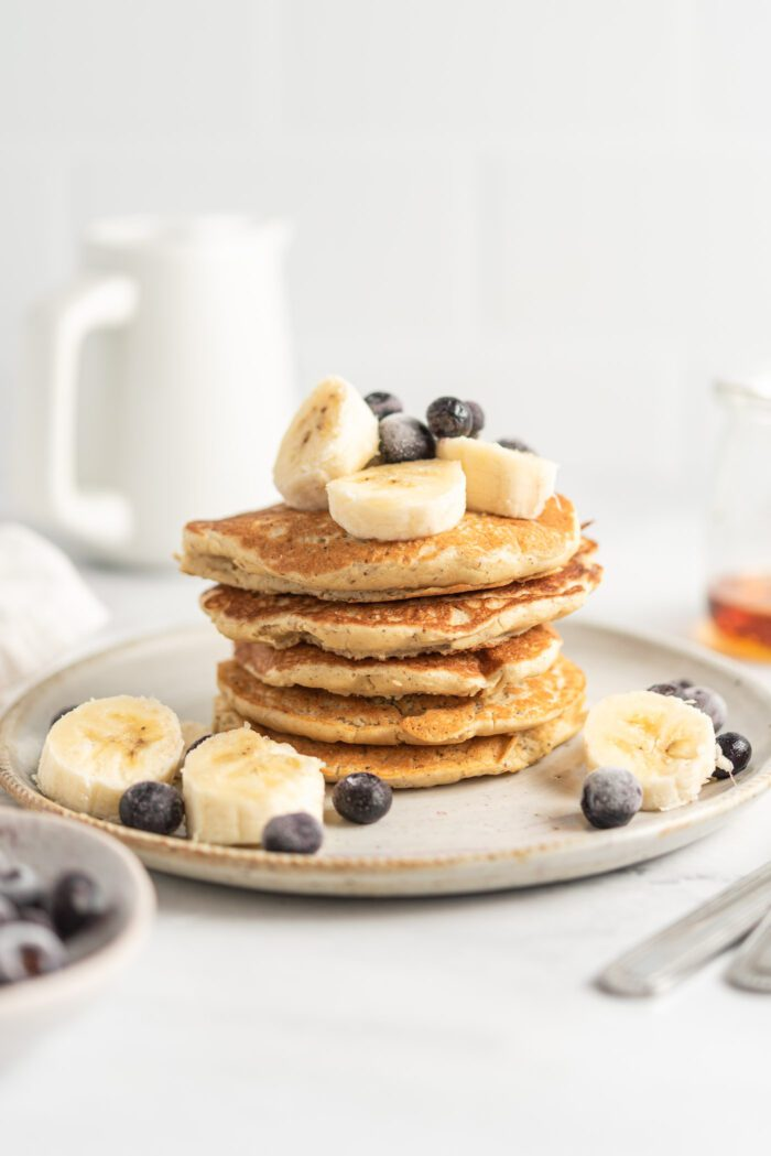 Stack of quinoa flour pancakes topped with blueberries and banana on a small plate. There's a small jug in the background and a small jar of maple syrup off to the side.