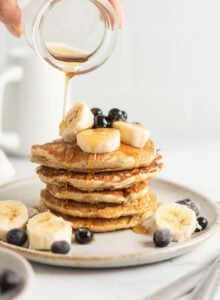 Hand pouring maple syrup from a small jar onto a stack of quinoa flour pancakes topped with banana and blueberry.