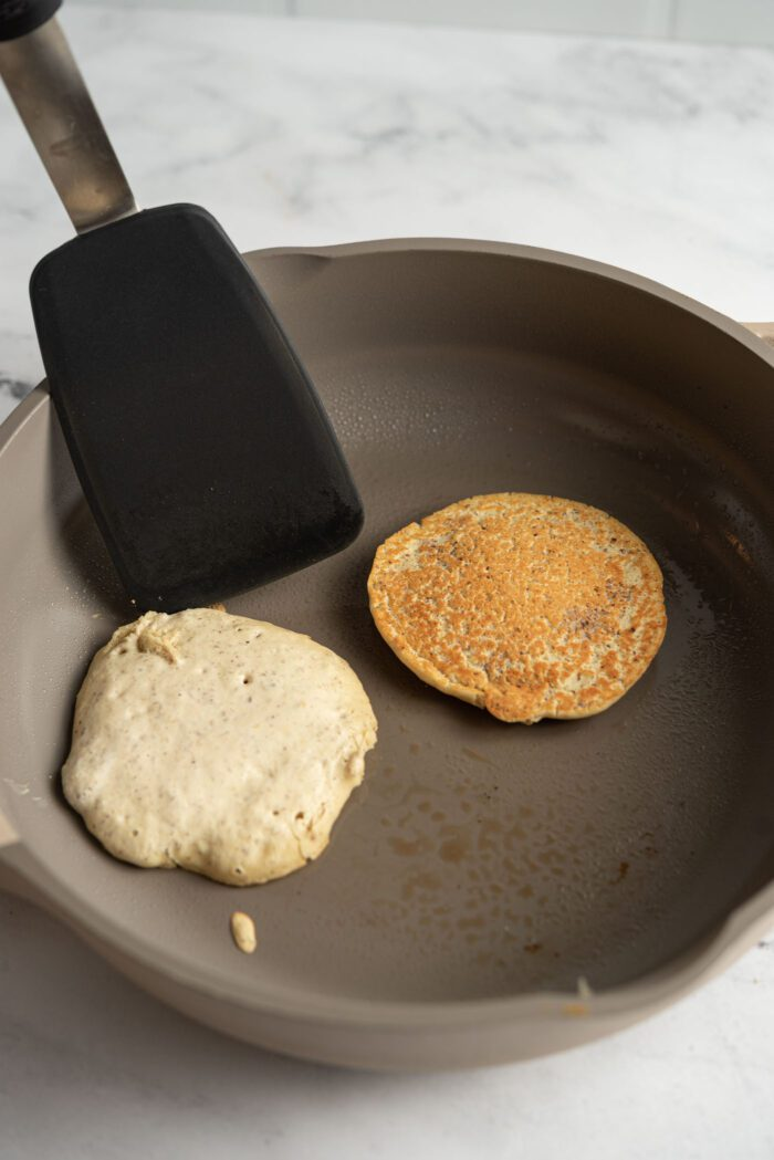 Spatula flipping a pancake in a hot skillet.