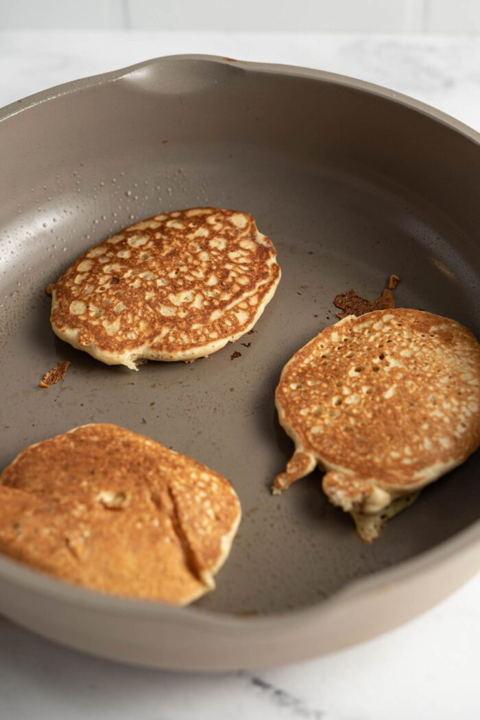 3 quinoa flour pancakes cooking in a skillet.
