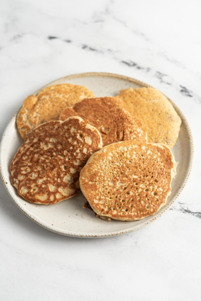 5 pancakes on a small plate on a marble surface.