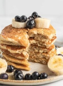 Close up of a stack of pancakes that have been sliced to show the texture inside. The pancakes are topped with blueberries and banana.