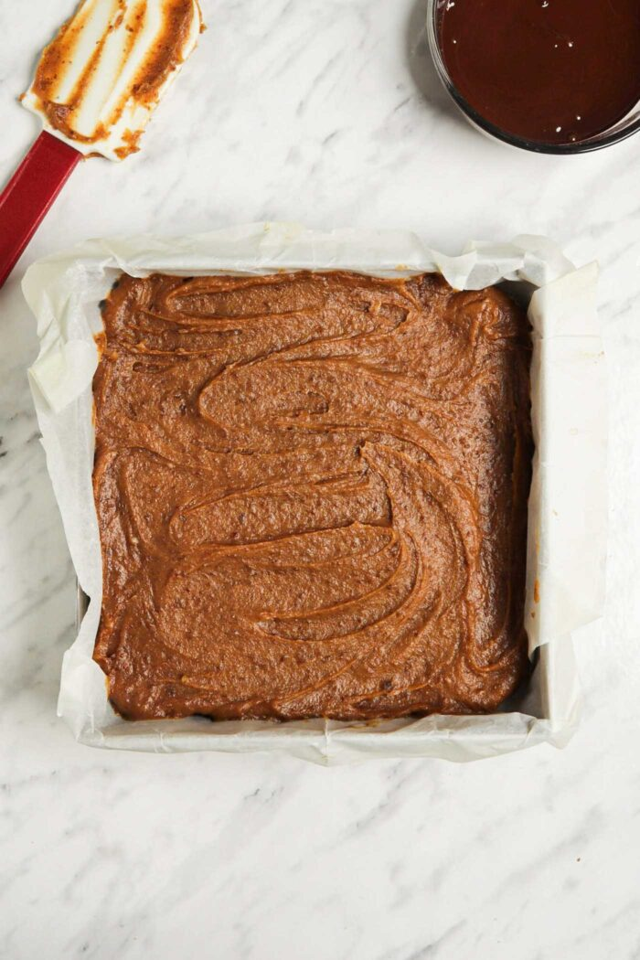 Date caramel spread into an even layer in a square baking pan.