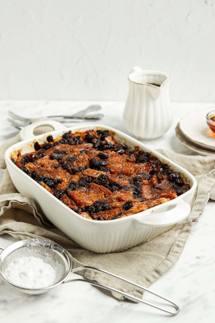 Baked bread pudding in a baking dish. A mesh strainer rests beside dish.