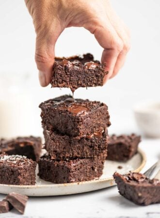 Hand lifting a chocolate brownie from a stack of 4 brownies on a plate.