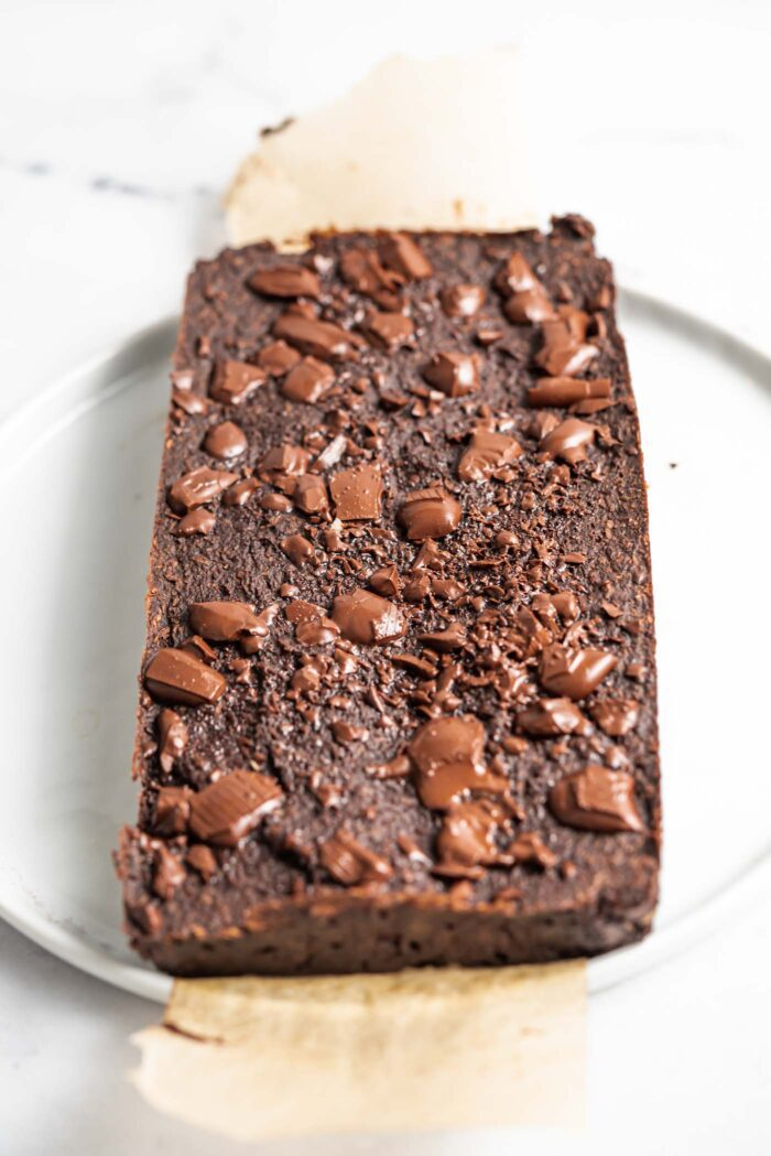 A slab of coconut brownies topped with chocolate chunks on a piece of parchment paper on a plate.