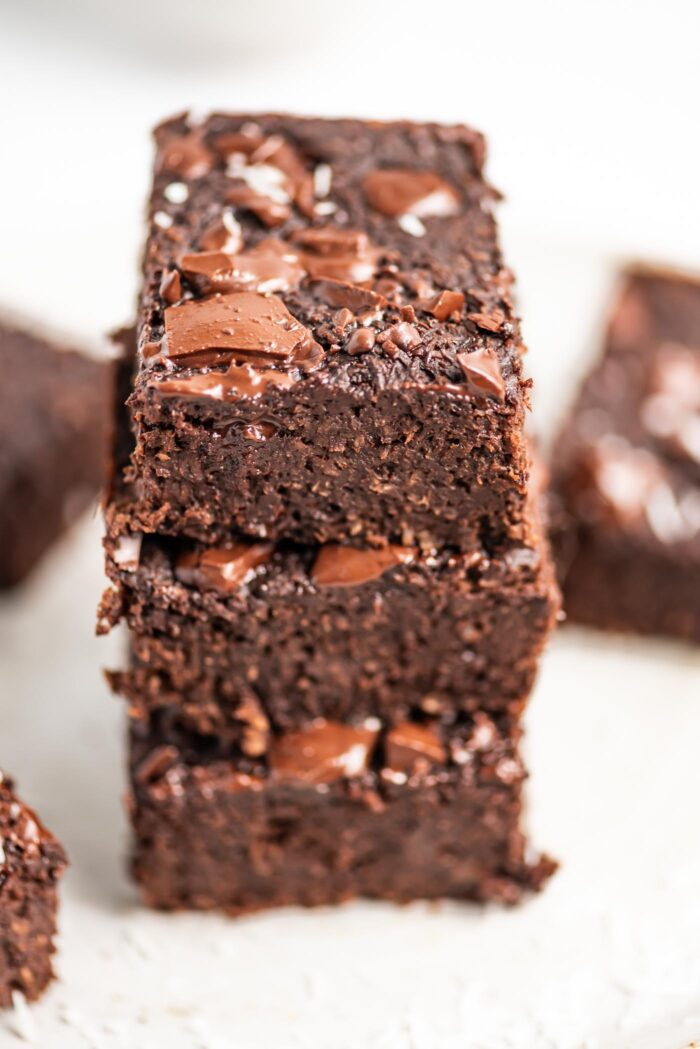 Close up of a stack of 3 coconut protein brownies topped with melted chocolate.