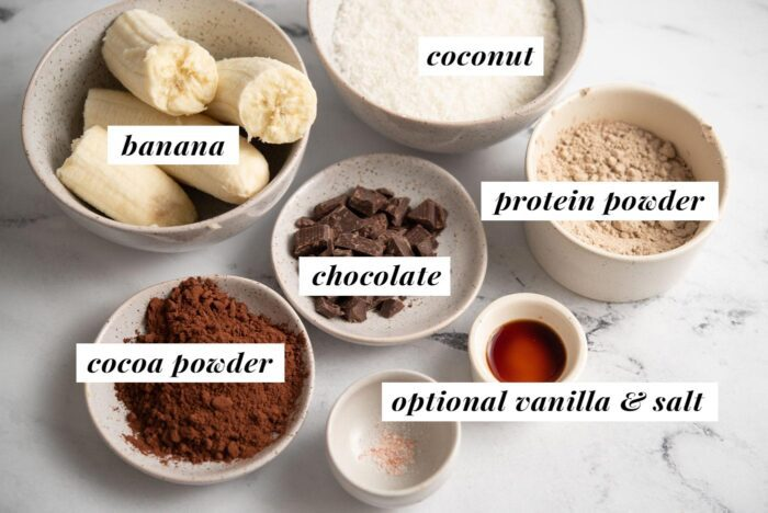 Visual of ingredients for making a coconut protein brownie recipe with banana, chocolate and protein powder.